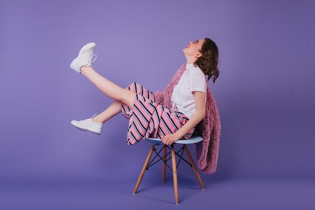 Модель красиво показывает длинные ноги на стуле в своей спальне