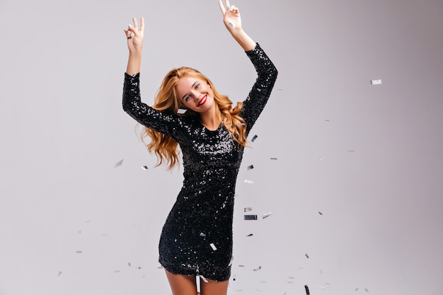 파티에서 춤을 추는 기분 좋은 잘 차려 입은 여자. 스파클 색종이 아래 포즈 검은 드레스에 귀여운 우아한 소녀. 무료 사진