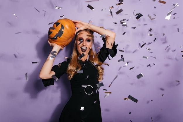 할로윈을 준비하는 기분 좋은 마녀. 파티에서 춤을 행복 금발 뱀파이어. 무료 사진