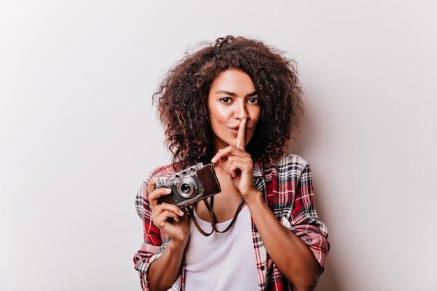 笑顔で立っているカメラを持つ気さくな若い女性。写真を撮る洗練された黒人の女の子。 無料写真