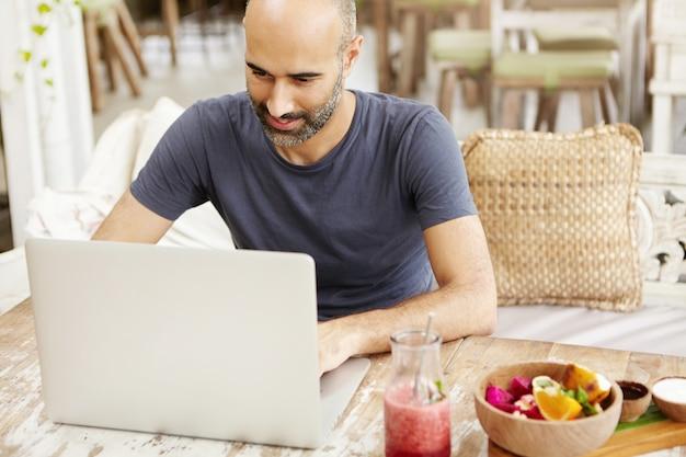 ひげのラップトップで電子メールをチェックし、カフェで無料の無線インターネット接続を使用し、朝食をとり、格好良い成人男性。 無料写真