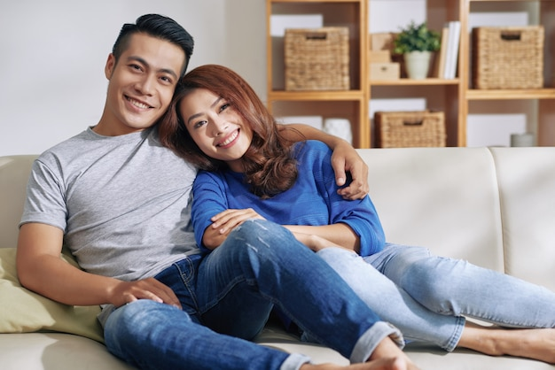 Good-looking asian couple relaxing on couch together at home and smiling Free Photo