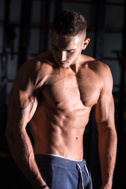 Good-looking athletic young man in gym Free Photo