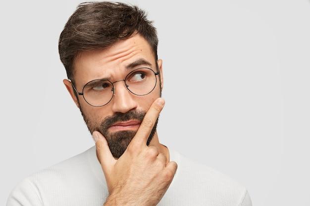 Bel giovane barbuto tiene il mento e guarda pensieroso da parte, solleva le sopracciglia e riflette su qualcosa Foto Gratuite