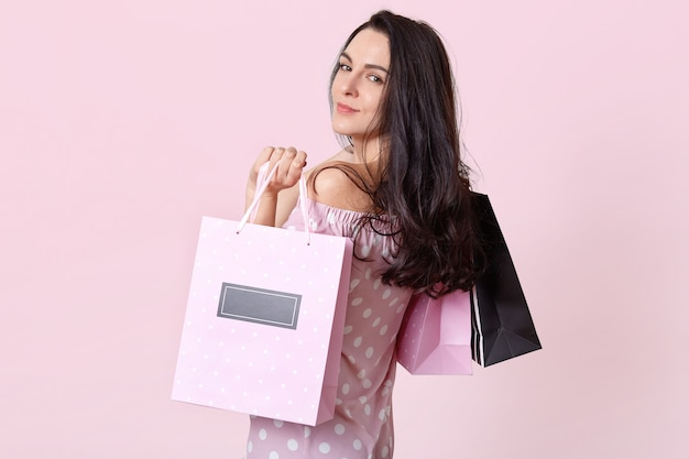 Good looking brunette woman stands sideways, holds shopping bags, returns from shopping mall in good mood, poses on pink. women and purchasing concept. Free Photo