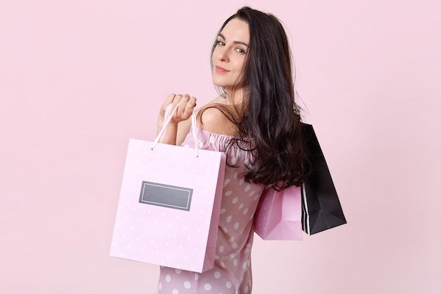 格好良いブルネットの女性は横に立って、買い物袋を保持している、良い気分でショッピングモールから戻った、ピンクのポーズ。女性と購入コンセプト。 無料写真