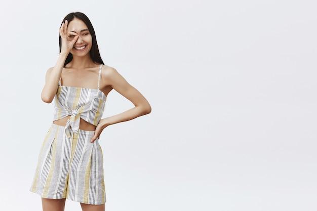 Modello di social media alla moda e spensierato di bell'aspetto in abito abbinato, che mostra il gesto ok o ok sull'occhio, tenendo la mano sulla vita e guardando da parte con un ampio sorriso felice sul muro grigio Foto Gratuite