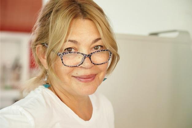 Красивая кавказская женщина средних лет со светлыми волосами и добрыми глазами, смотрящая с нежной и дружелюбной улыбкой, ожидая, когда ее внуки навестят ее дома во время летних каникул. Бесплатные Фотографии