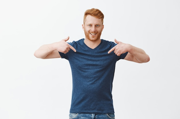 Good-looking confident and proud redhead male model with bristle in blue t-shirt, pointing at himself with index fingers and smiling Free Photo