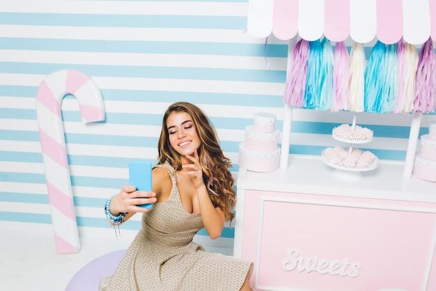 美味しいお菓子が並ぶケーキショップの前でヴィンテージのドレスを着てセルフィーを作る格好良い巻き毛の女の子カウンターの近くの縞模様の壁の上に座って青い電話でかわいい陽気な女性の屋内ポートレート。 無料写真