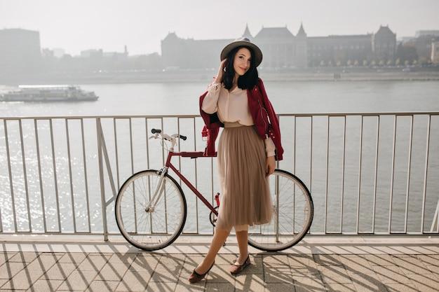 川の近くで時間を過ごすスカートのハンサムな黒髪の女性 無料写真