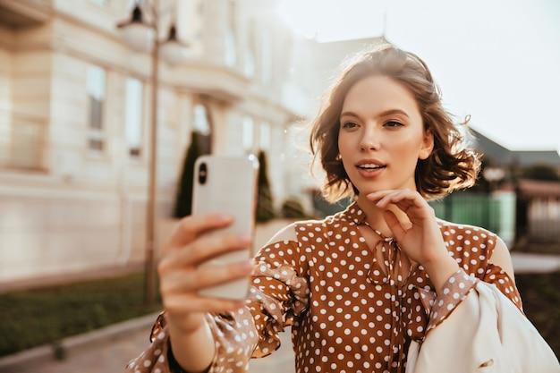 スマートフォンを持って自分撮りをしている格好良いエレガントな女性。通りでポーズをとる茶色のドレスを着た素晴らしいヨーロッパの女性。 無料写真