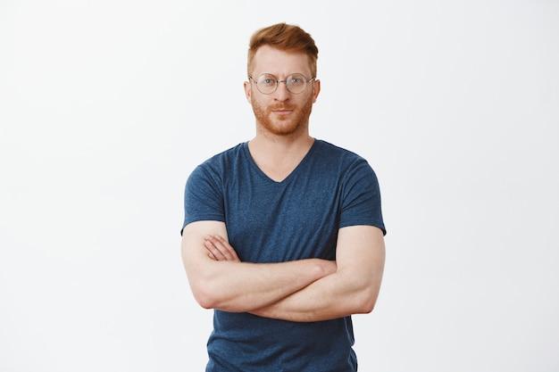 Bell'uomo d'affari europeo con capelli rossi e setole in freschi occhiali trasparenti, dita incrociate sul petto Foto Gratuite