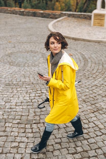 携帯電話と傘を片手に都市公園を通り抜けて休みを楽しんでいる美しい女性 無料写真