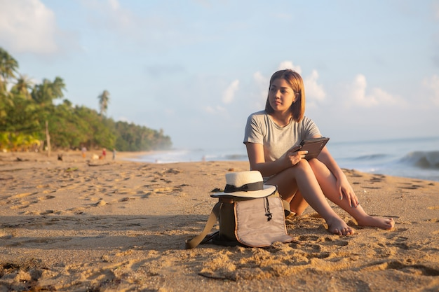 Good looking girl sit and play smartphone on beach Premium Photo