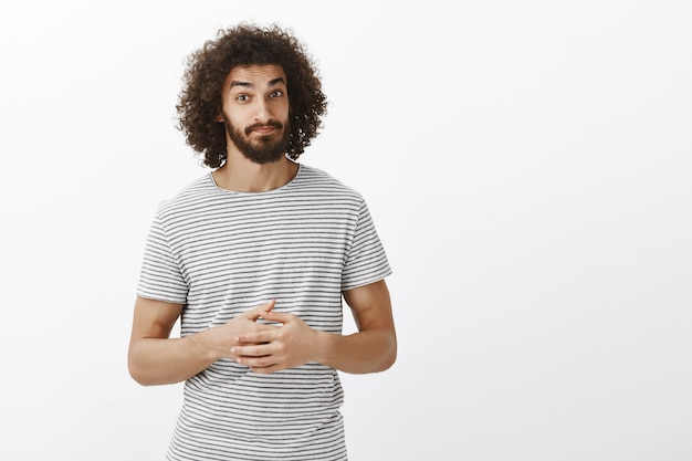 Good-looking hispanic bearded male coworker with curly hairstyle in striped t-shirt, clenching palms together, looking doubtful Free Photo