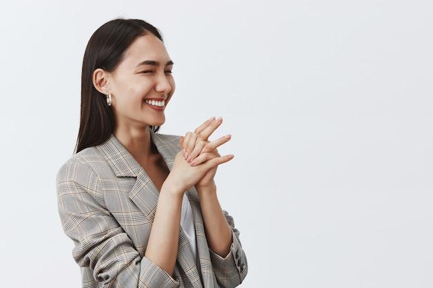 Bella donna allegra che ride di gioia ed entusiasmo, in piedi mezzo capovolto sul muro grigio, stringendo le mani insieme, guardando a destra Foto Gratuite