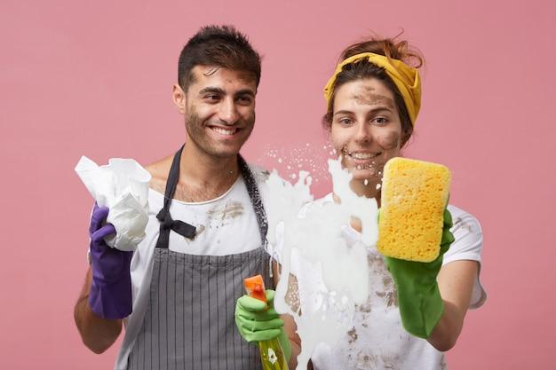 保護手袋とエプロンを身に着けているかっこいい男性が妻の洗濯窓を見ている。陽気な女性が夫と一緒に掃除しながらスポンジを使用してシャワーでガラス表面から濃い泡を拭く 無料写真