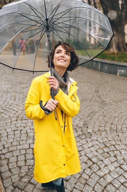 市庭の広い誠実な笑顔と大きな透明な傘の下に立っている黄色のレインコートで見栄えの良い大人の女の子 無料写真