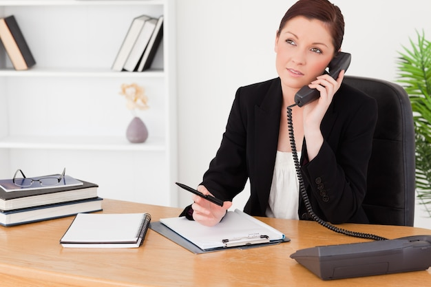 Good looking redhaired woman in suit writing on a notepad and phoning Premium Photo