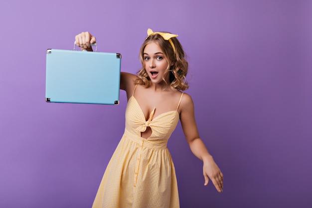 Bella signora magra con pelle abbronzata in posa con valigia. ritratto dell'interno della ragazza bionda felice con la valigia blu. Foto Gratuite