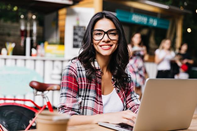 Симпатичная умная девушка позирует с улыбкой на улице. удивительная брюнетка женщина, использующая ноутбук в выходные утром. Бесплатные Фотографии