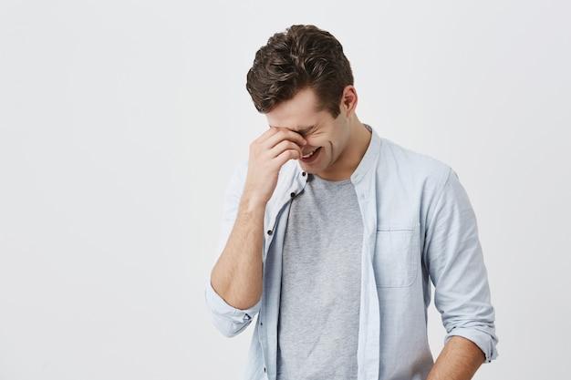 おしゃれなトレンディな若い白人男性モデル。灰色のtシャツの上に水色のシャツを着てスタイリッシュな散髪をし、笑ったり、友達の冗談や面白い話を笑ったり、鼻の橋に触れたりします。 無料写真