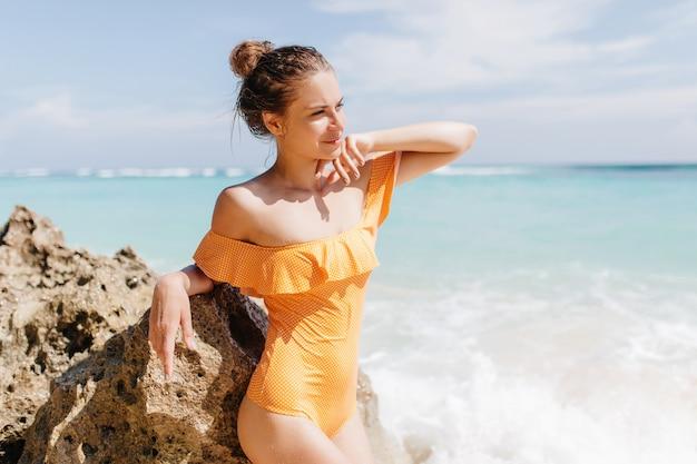 Красивая белая девушка в ретро купальниках, глядя в сторону. модная шатенка в желтой одежде, стоя на берегу океана и трогательно скале. Бесплатные Фотографии