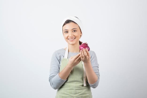 보라색 양파를 들고 앞치마에 잘 생긴 여자 모델. 무료 사진