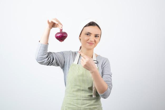 보라색 양파를 가리키는 앞치마에 잘 생긴 여자 모델. 무료 사진