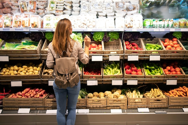 Good looking woman standing in front of vegetable shelves choosing what to buy Free Photo