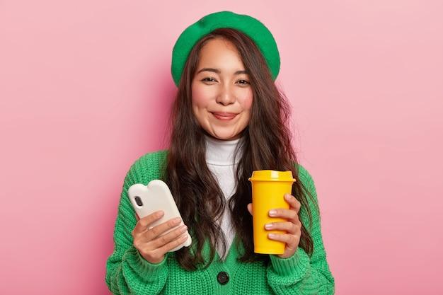 검은 스트레이트 헤어, 루즈 뺨을 가진 잘 생긴 여성은 흰색 휴대 전화와 커피 컵을 들고 소셜 네트워크 서핑을위한 자유 시간을 즐깁니다. 무료 사진