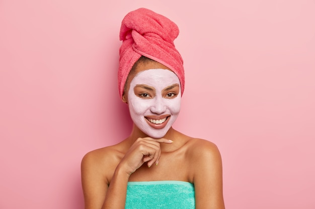 Good looking woman with pleased expression, touches chin gently, wears cleansing clay mask on face, has wrapped towel on head, enjoys beauty treatments at home, isolated on pink wall Free Photo
