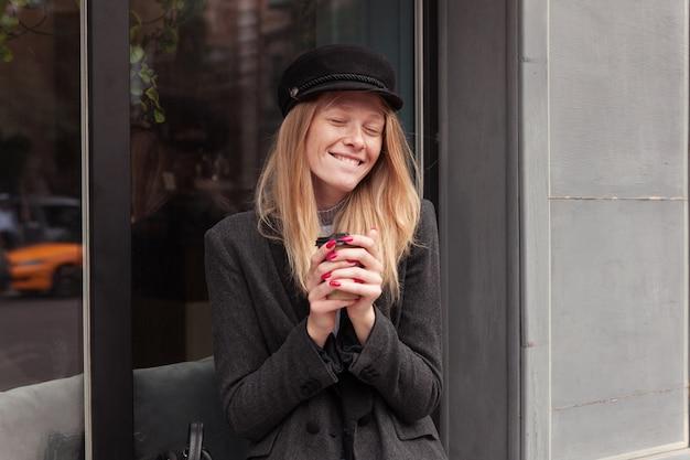 エレガントな灰色の服を着て、コーヒーを飲みながら窓辺に座って目を閉じて幸せそうに笑っているカジュアルな髪型の格好良い若い陽気なブロンドの女性 無料写真