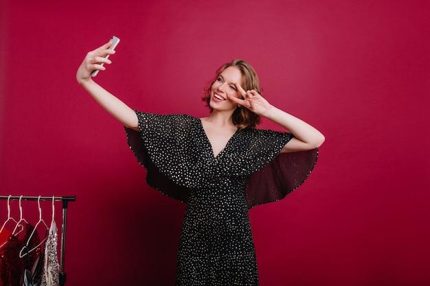 Красивая молодая женщина-модель с татуировкой, фотографирующая себя в гримерной Бесплатные Фотографии