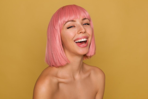 Good looking young happy pretty lady with short pink hair throwing back her head while laughing cheerfully, being in nice mood while posing over mustard background Free Photo