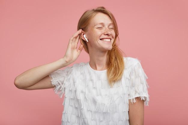 ピンクの背景の上にポーズをとっている間、彼女の頭に手を上げて、彼女のイヤホンで音楽トラックを楽しんでいる間目を閉じたままにして、自然なメイクで格好良い若い幸せな赤毛の女性 無料写真