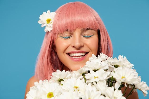흰색 꽃에서 포즈를 취하는 동안 축제 메이크업을 입고 짧은 분홍색 머리를 가진 좋은 찾고 젊은 행복한 여자, 닫힌 눈으로 즐겁게 웃고 무료 사진