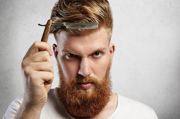 Bello giovane con la barba rossa che tiene l'accessorio da barbiere. barbiere caucasico che mostra la lama affilata del suo vecchio rasoio a mano libera, determinato a radere i clienti. Foto Gratuite