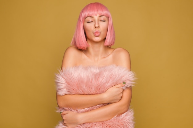 Good looking young pretty lady with short pink hair holding fluffy pillow while posing over mustard wall, folding lips in air kiss with closed eyes Free Photo