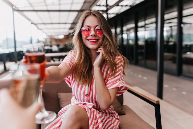 Красивая молодая женщина, держащая коктейль и улыбаясь в летний день. восторженная блондинка в розовых очках расслабляется с бокалом вина в выходные. Бесплатные Фотографии