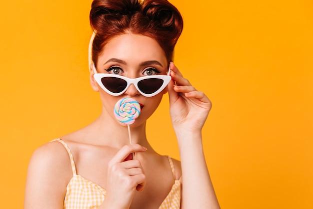 하드 캔디를 핥는 잘 생긴 젊은 여자. 선글라스에 생강 핀 업 소녀의 전면 모습. 무료 사진