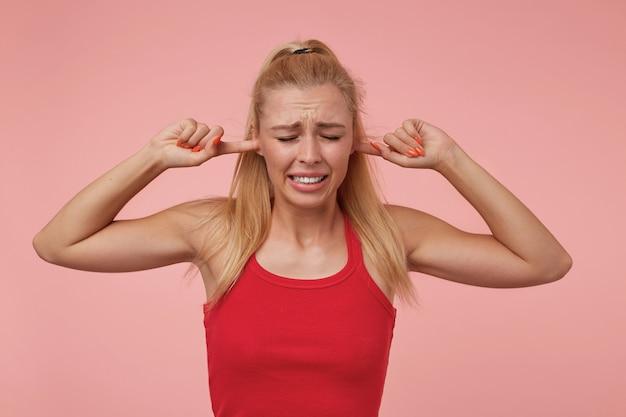 Bella giovane donna con acconciatura casual in piedi, che copre le orecchie con le mani e rughe, cercando di evitare suoni forti Foto Gratuite