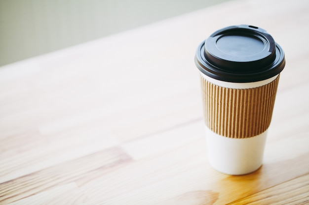 Good morning, coffee time, coffee to go and beans on a wooden background Premium Photo