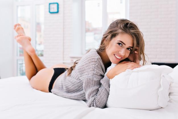 Доброе утро, просыпающаяся привлекательная молодая женщина в вязаном свитере и черном бикини. красивая девушка с длинными волосами брюнет охлаждая на кровати в современной квартире. улыбка, удовольствие, настоящие эмоции. Бесплатные Фотографии