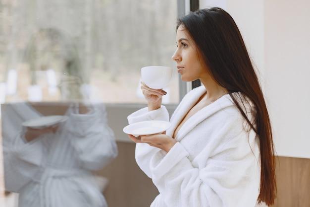 おはようございます。女性はコーヒーを飲みます。窓際の女性。 無料写真