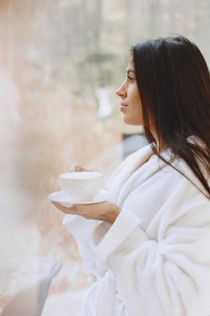 Good morning. woman drinks coffe. lady by the window. Free Photo