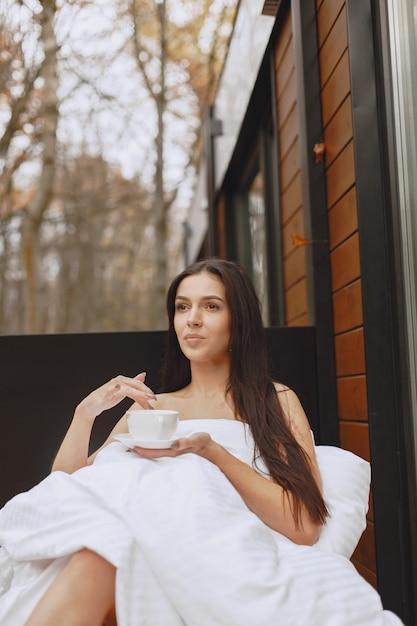 おはようございます。毛布の中の女性。テラスに座っている女性。ブルネットはコーヒーを飲みます。 無料写真