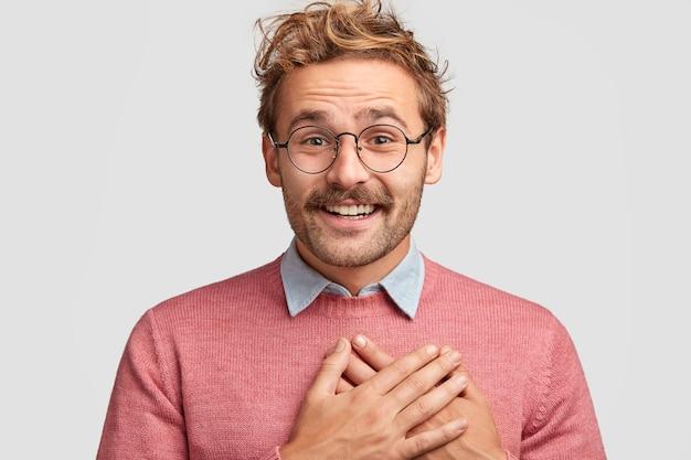 気さくなヒップスターの男性は胸に手を当て、ポジティブな表情、巻き毛のトレンディな髪型を持ち、ゲストに感謝しています 無料写真