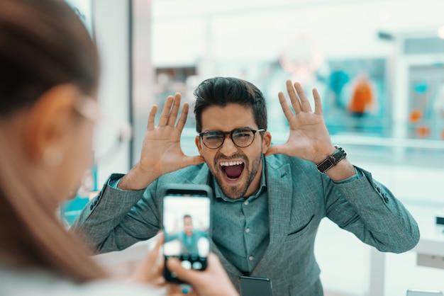 Пара, пробующая новый смартфон в техническом магазине. женщина принимая фото ее мужа goofing вокруг. Premium Фотографии